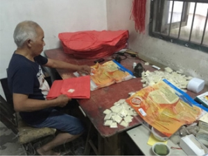 A villager is packing flying lantern in his home