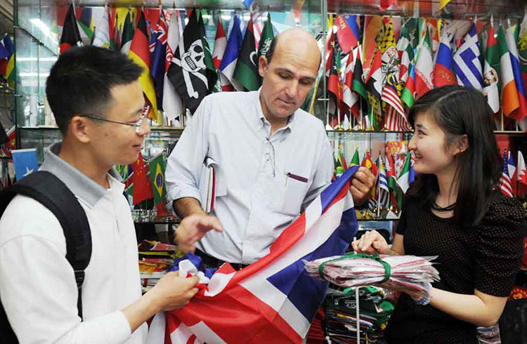 A foreign customer is visiting a flag booth with an agent